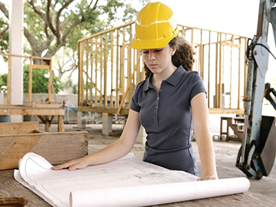 female construction worker looking at blueprints